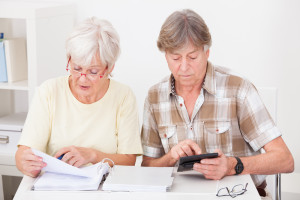 Elderly Woman Checking The Accounts While The Husband Adds Up The Figures On The Calculator