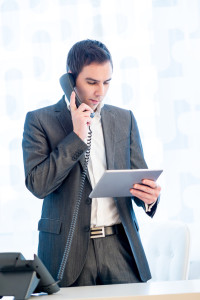 Businessman standing in his office talking on the telephone while checking his tablet computer at the same time.